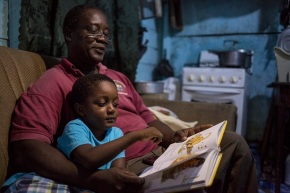 """On 16 August 2016 in Belize, Marshall Mejia reads a bedtime story to his son, 4-year-old Orin Mejia, in the home of Orin's mother, in the town of Dangriga, on the south-eastern coast. Orin, whose parents are not together, stays at his mother's home at night-time and with his father, Marshall Mejia, during the day. His father's house is two minutes away by bicycle, and both homes are located just a few hundred metres from the sea. Mr. Mejia, who is a preschool teacher, understands the importance of exposing children to learning materials and a stimulating environment from a young age. """"We must prepare children for school long before they arrive in the classroom, only then are they able to benefit fully from the teachings,"""" he says. Orin, who graduated from the Kids First Child Development Centre preschool and begins primary school in September, has a wide-ranging vocabulary. He loves to read, or be read to by his father at bedtime. Mr. Mejia's activities with his son also include trips to the seaside – to swim at the beach and to see what fishermen at the pier have caught – and to the park to play.  In recent years, considerable progress was made in the area of Early Childhood Development. In 2011 only 32 per cent of children between 36 and 59 months of age attended an Early Childhood Education (ECE) programme, but this reached 55 per cent by 2015. Disparities however persist as only one in five of the poorest children attend ECE, and the Cayo district sees the lowest ECE attendance rate (36 per cent).  Further success is contingent upon removing barriers to supply of services, such as sufficient number of qualified professionals and greater integration of the different ECD components. The recent adoption of a national ECD policy demonstrates the Government's commitment to strengthening ECD services.    UNICEF and the World Health Organization (WHO), with their national, regional and country partners, promote the use of a range of effective interv"""
